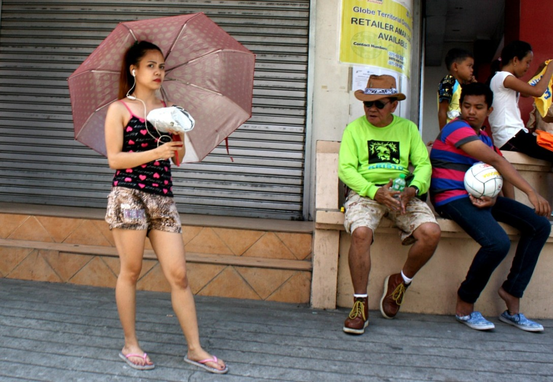 Rizal Street, Iriga City. Two men laying eyes on a lady.