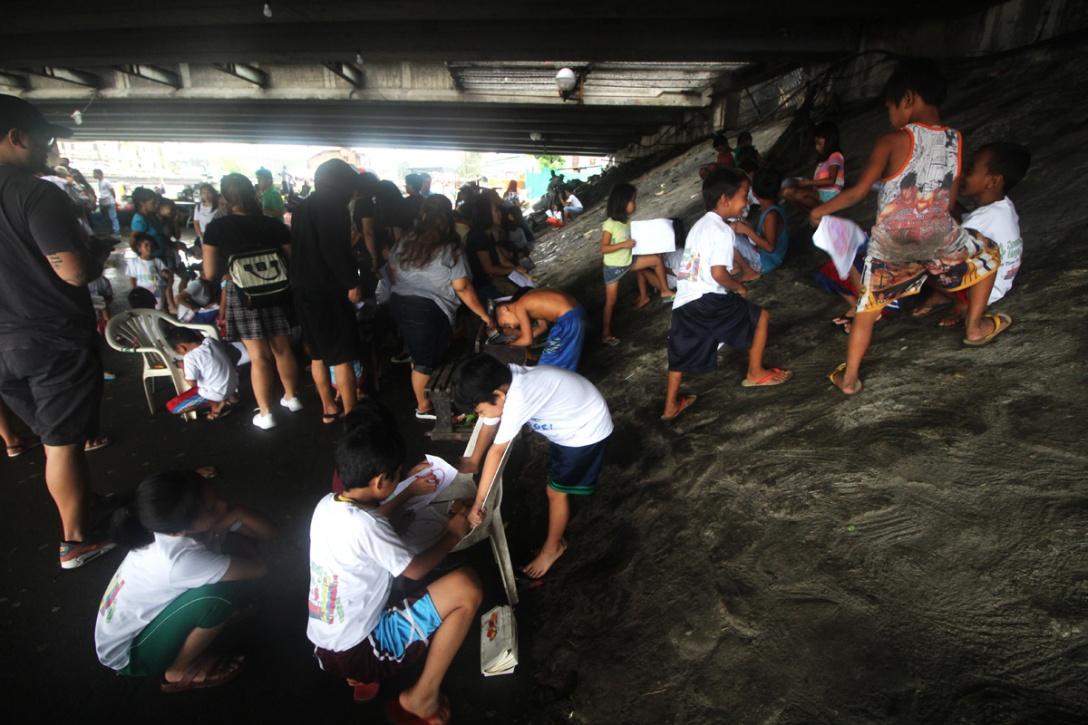 Students holding class under a bridge.