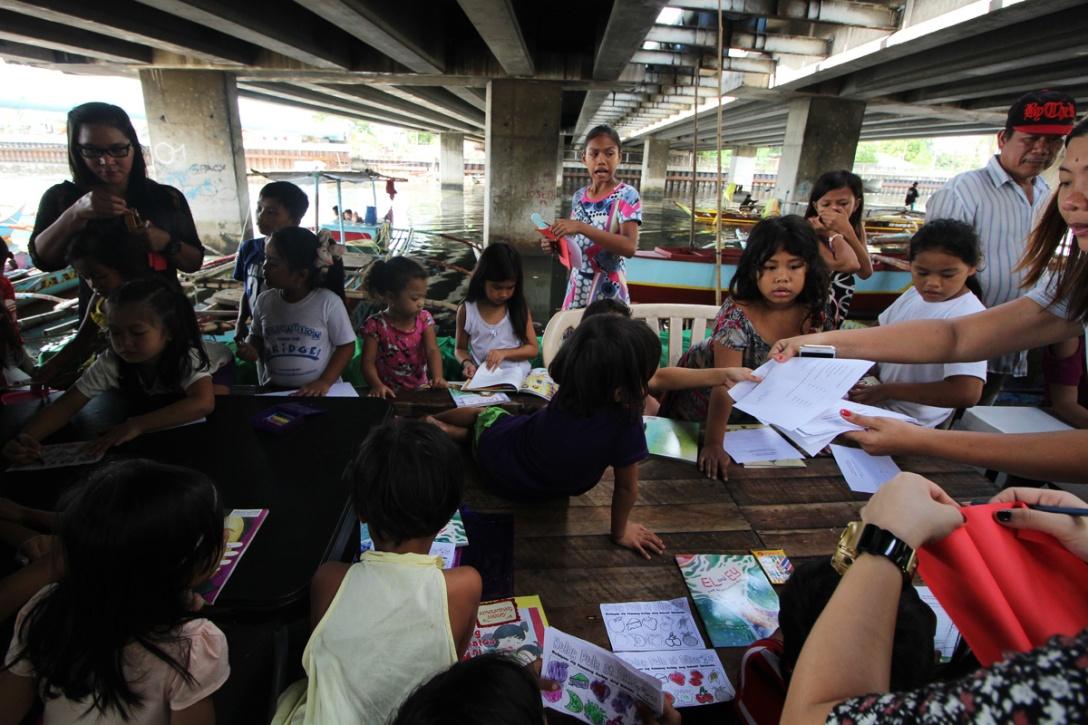 Children holding class under the bridge.