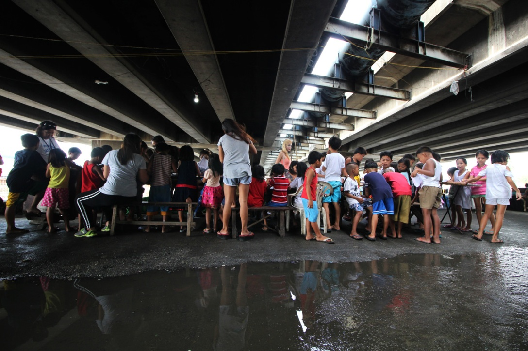 Young students gathering underneath a bridge