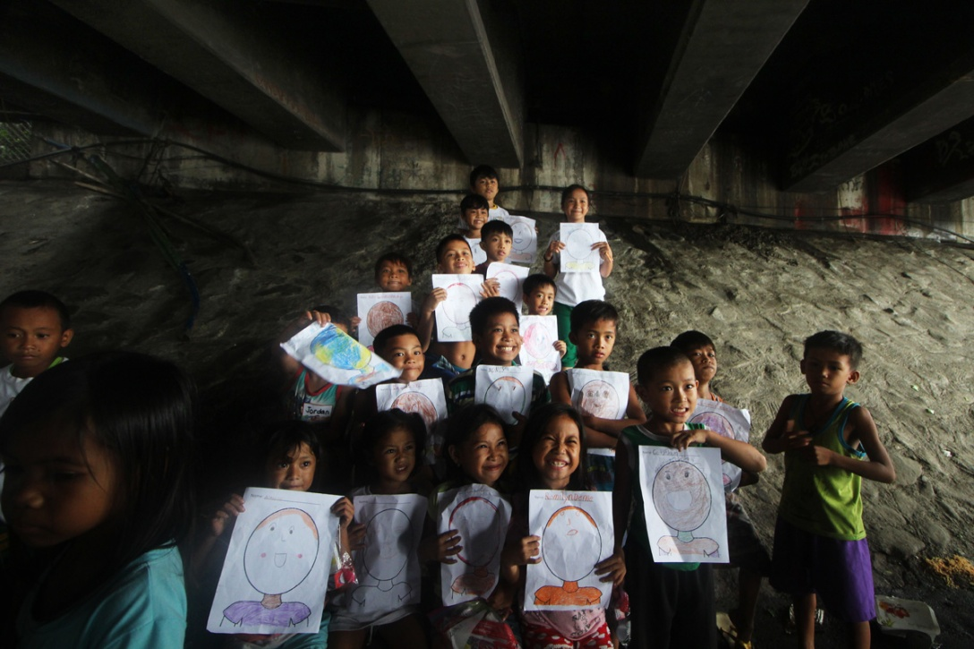 Photo of young students showing off their artwork.