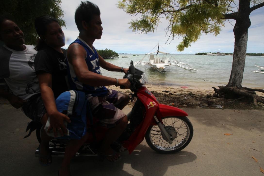 Motorcycle passing through San Vicente Road Olango Island