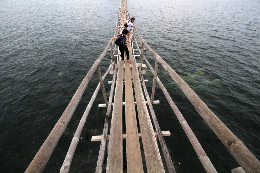 Visitors crossing a gangplank over Hilatungan Channel in Olango Island