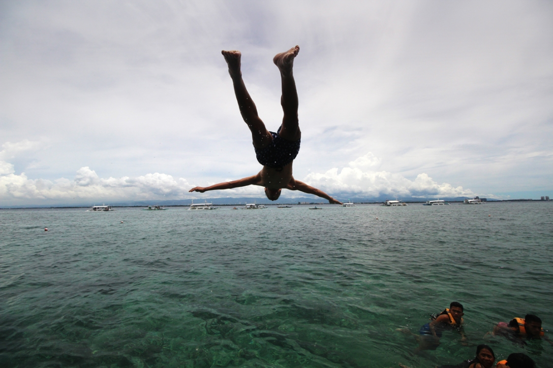 A diver caught in mid-air plunging to the Hilatungan Channel in Olango Island